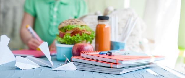 Schoolmeisje en lunch. boeken en schriften voor school.