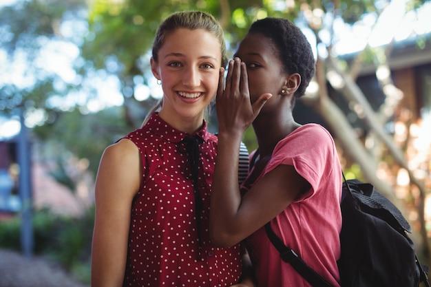 Schoolmeisje fluistert in het oor van haar vriend
