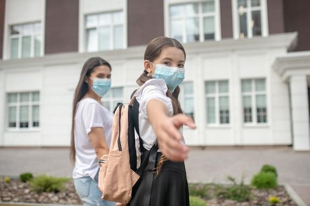 Schoolmeisje haar hand uitrekken met uitnodiging voor camera met moeder in beschermende maskers wandelen in de buurt van school