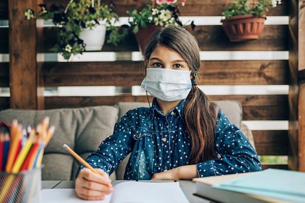 Schoolmeisje huiswerk kijken naar computer met medische masker op haar gezicht.