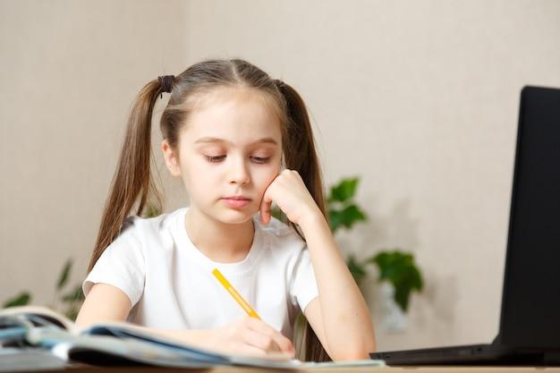 Schoolmeisje huiswerk studeren tijdens haar online les thuis, online onderwijs en online schoolconcept, huisschooler. leren op afstand of op afstand