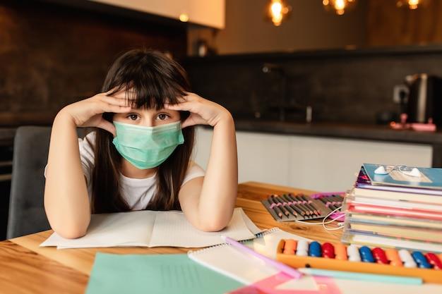 Schoolmeisje in beschermend masker op het gezicht. depressie en hoofdpijn door online leren thuis.