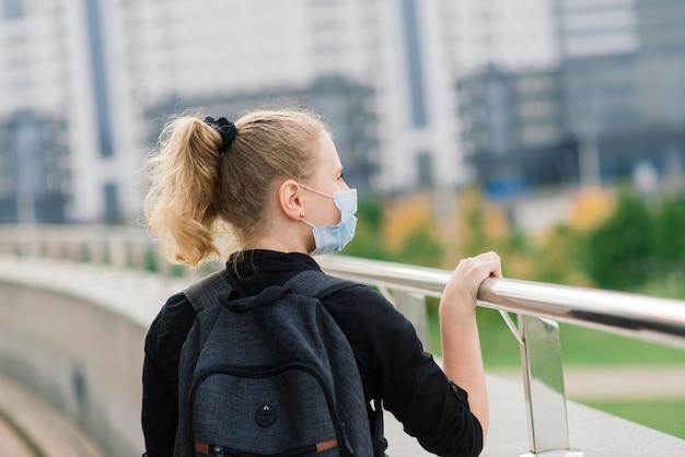 Schoolmeisje in beschermend medisch masker bij zonsondergang. moderne leerling met rugzak tijdens de covid-19 quarantaine.