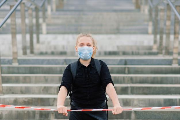 Schoolmeisje in beschermend medisch masker bij zonsondergang.