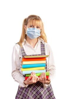 Schoolmeisje in een beschermend medisch masker houdt een stapel boeken op een witte achtergrond.