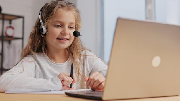 Schoolmeisje in hoofdtelefoon heeft online les, videogesprek met leraar, vragen beantwoorden, kennis controleren.