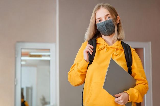Schoolmeisje in masker met rugzak en kladblok. jonge vrouwelijke student met beschermend medisch masker. portret van blonde vrouwelijke student girl aan het interieur van de universiteit tijdens coronavirus covid 19 lockdow.