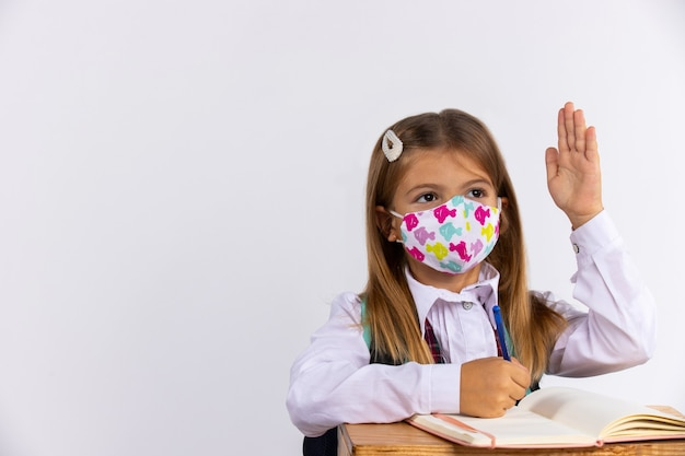 Schoolmeisje in medisch masker, hief haar handen op bij les, trainingsboeken op tafel. school concept