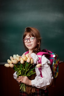 Schoolmeisje in schooluniform met in hand bloemen, tulpen, op rug schoolrugzak