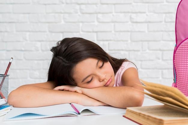 Schoolmeisje in slaap met hoofd op voorbeeldenboek