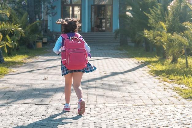 Schoolmeisje in uniform gaat naar school, onderwijs.