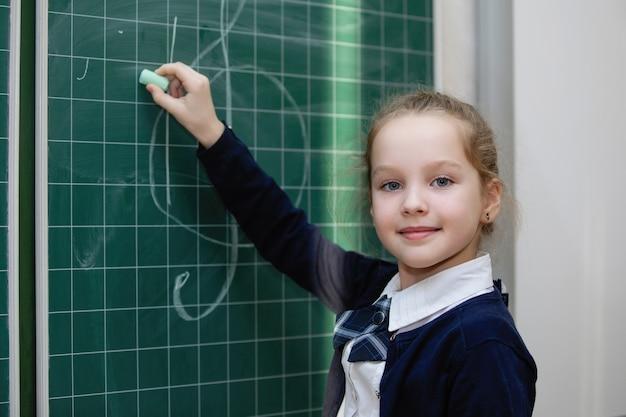 Schoolmeisje in uniform schrijft met krijt op een schoolbord. school basisonderwijs. selectieve aandacht.