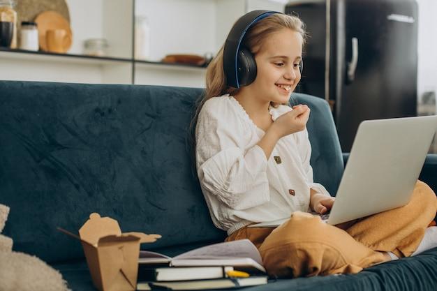 Schoolmeisje kijken naar film op computer en eten popcorn