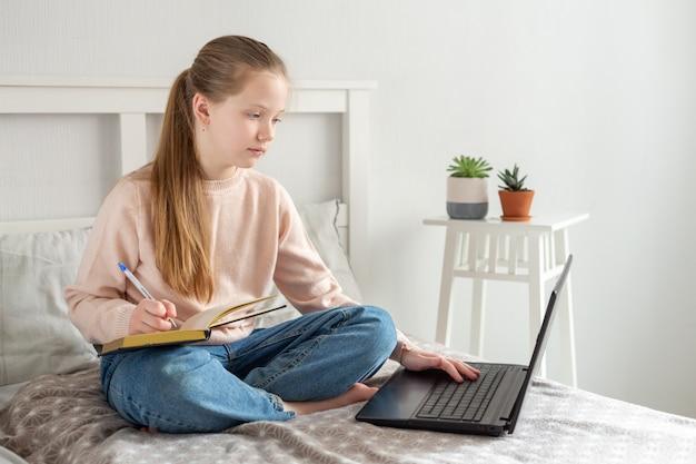 Schoolmeisje kijkt naar een laptop scherm. online onderwijs, quarantaineconcept