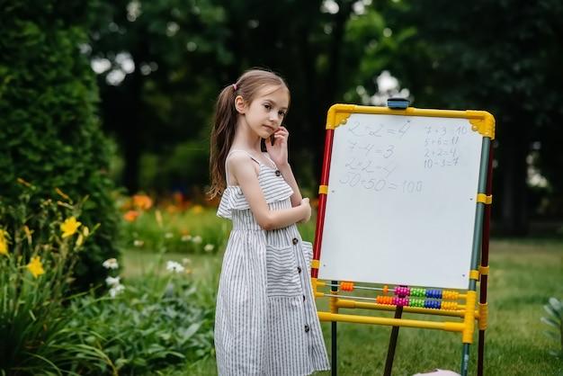 Schoolmeisje leert in de open lucht over het bord