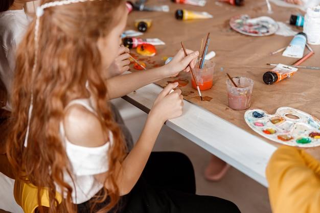 Schoolmeisje leert schilderen met waterverf op school