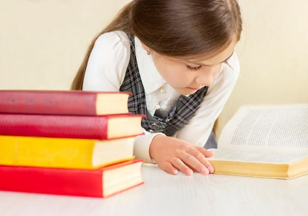 Schoolmeisje leest een boek aan een tafel met een stapel boeken