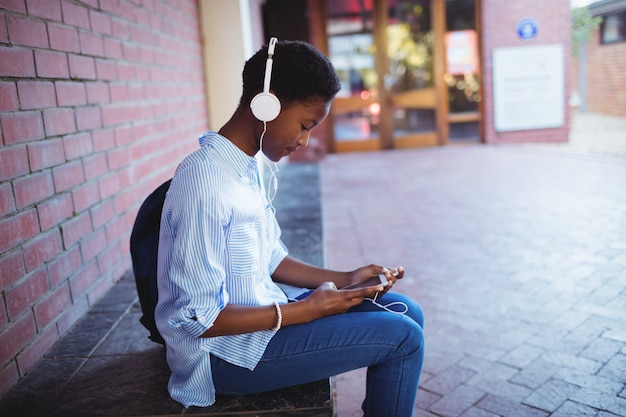 Schoolmeisje luisteren muziek op mobiele telefoon
