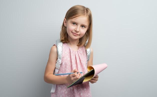 Schoolmeisje maken van aantekeningen in schrijfblok