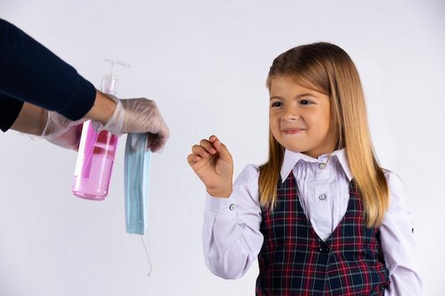 Schoolmeisje meisje, na het desinfecteren van haar handen, wil voorzichtig een masker nemen voordat ze het klaslokaal binnengaat, geïsoleerd op een witte muur. virus en pandemie concept.