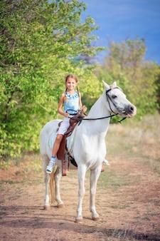 Schoolmeisje meisje rijdt op een witte pony. het kind rijdt op een paard. paardrijtraining voor kinderen. het paard besturen met de teugels