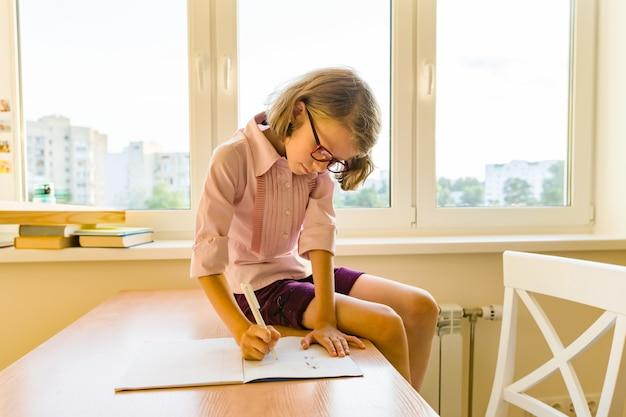 Schoolmeisje, meisje van 8 jaar, zittend aan tafel met boeken en schrijven in notitieblok. school, onderwijs, kennis en kinderen.