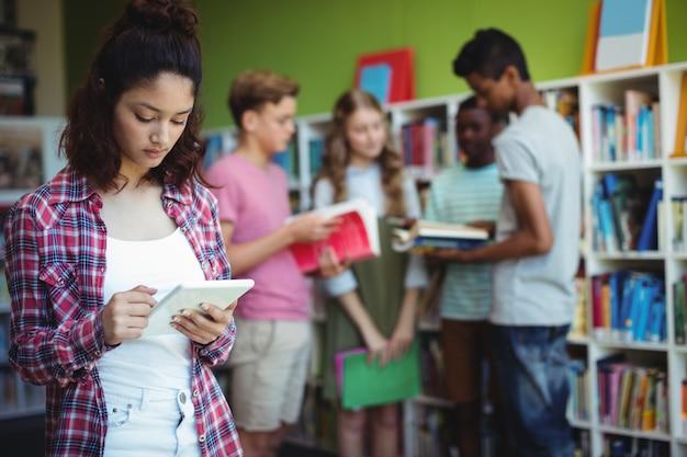 Schoolmeisje met behulp van digitale tablet in bibliotheek