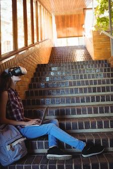 Schoolmeisje met behulp van virtual reality headset en laptop op trap