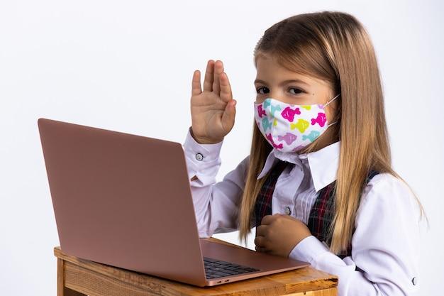Schoolmeisje met beschermend gezichtsmasker met hand omhoog zit in haar bureau op school na covid-19. isolatie - sociale afstand op school. in quarantaine plaatsen en afsluiten ...