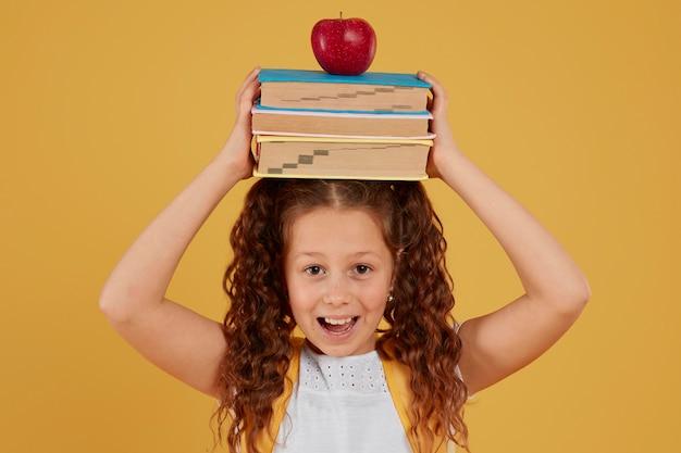 Schoolmeisje met boeken en appel op haar hoofd