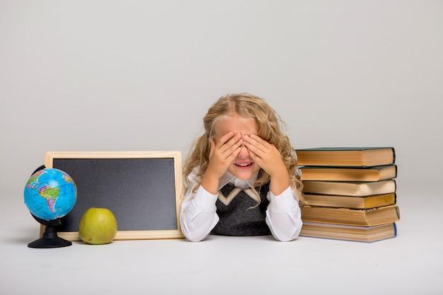 Schoolmeisje met boeken en leeg tekenbord op witte achtergrond