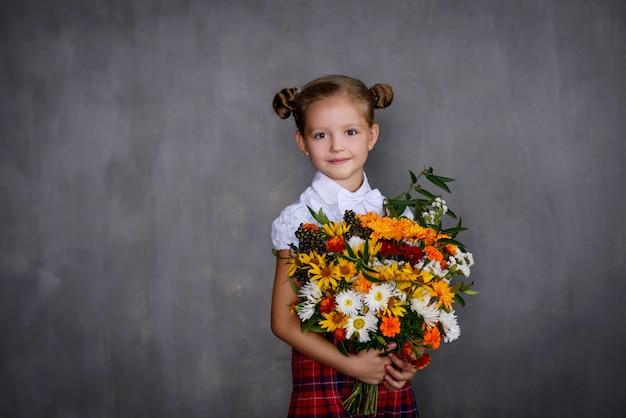 Schoolmeisje met boeket bloemen. school concept