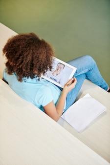 Schoolmeisje met digitale tablet die online les heeft en belangrijke details in leerboek schrijft