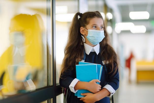 Schoolmeisje met een beschermend masker met een rugzak en een leerboek.