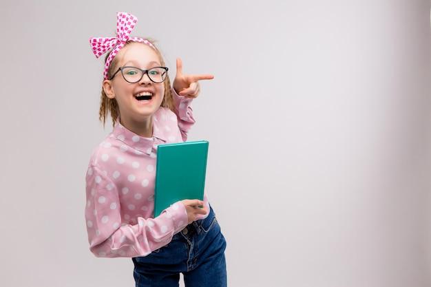 Schoolmeisje met een bril met een boek glimlachen
