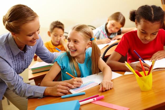 Schoolmeisje met een goede tijd met de leraar