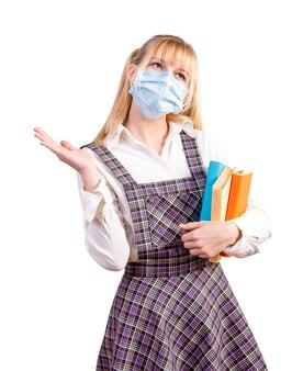 Schoolmeisje met een medisch masker op haar gezicht houdt schoolboeken op een wit