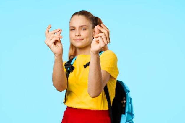 Schoolmeisje met een rugzak gebaren met haar handen op een blauwe achtergrond en een geel t-shirtmodel