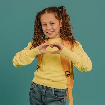 Schoolmeisje met geel overhemd dat een hartvorm maakt