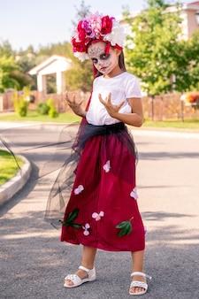 Schoolmeisje met geverfd gezicht in halloween kostuum hand in hand voor zichzelf terwijl ze naar je kijkt met een sombere uitdrukking op zonnige dag