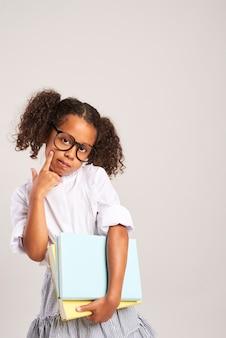 Schoolmeisje met hand op kin denken