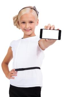 Schoolmeisje met mobiele telefoon in de hand kijken naar de camera