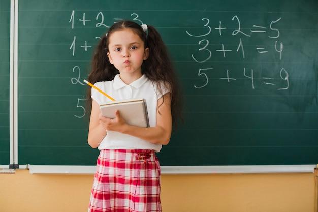 Schoolmeisje met notitieblok grimacing