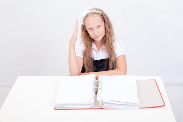 Schoolmeisje met rode mappen zittend aan tafel op witte achtergrond