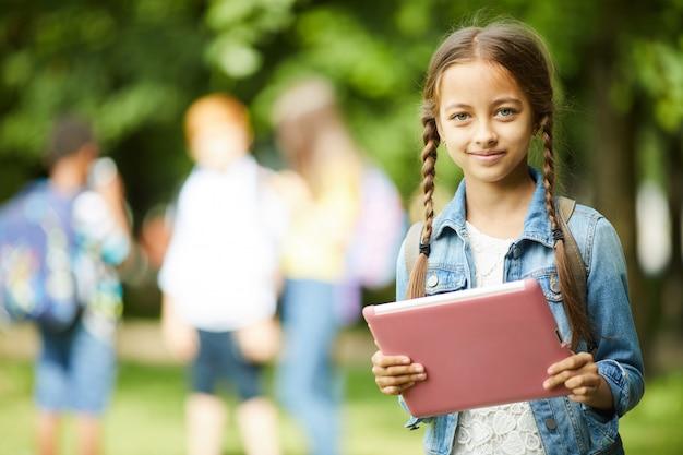 Schoolmeisje met roze tablet