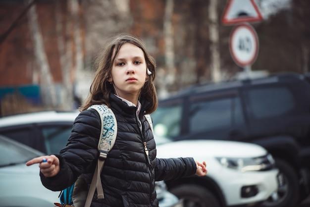 Schoolmeisje met rugzak wandelingen langs stad straat bij bewolkt weer in de regen