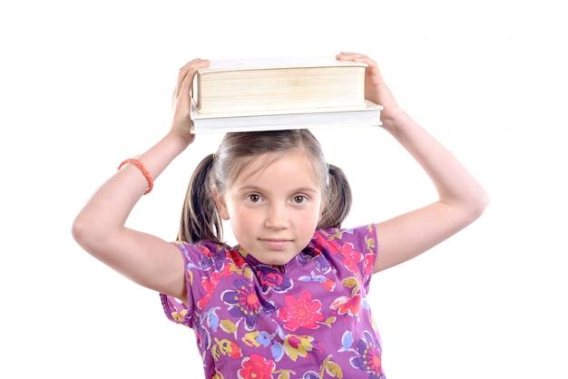 Schoolmeisje met stapel boeken op hoofd