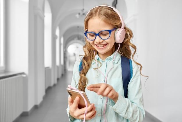 Schoolmeisje met telefoongesprek houden en muziek luisteren
