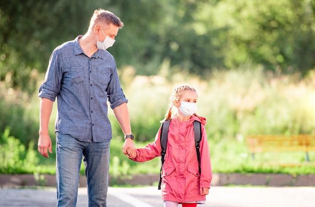 Schoolmeisje met vader in medische maskers die terug naar school gaan
