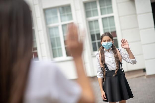 Schoolmeisje met vrolijke ogen in beschermend masker en shrukzak die afscheid neemt van haar moeder die haar hand opheft